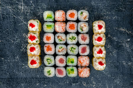 Various kinds of sushi food served on black stone, sushi rolls composition top view