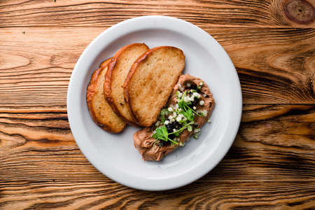 Delicious chicken, duck, or rabbit liver pate or foie gras with spices. Beautiful stylish menu. Autumn still life. Free space for text. fried toast and pate with microgreens