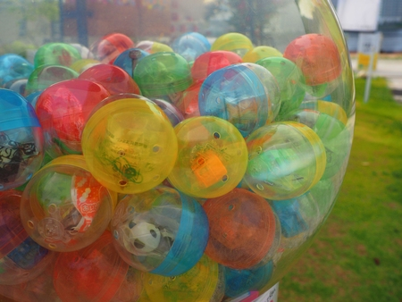 small toy in colorful ball in kid game vendor machine 写真素材