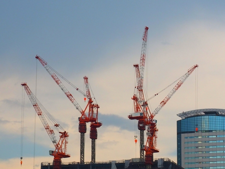 Industrial construction cranes and building silhouettes 写真素材