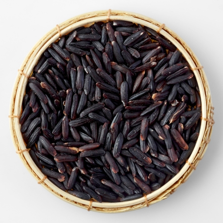 Thai black jasmine rice (Riceberry)in bamboo basket isolated on white