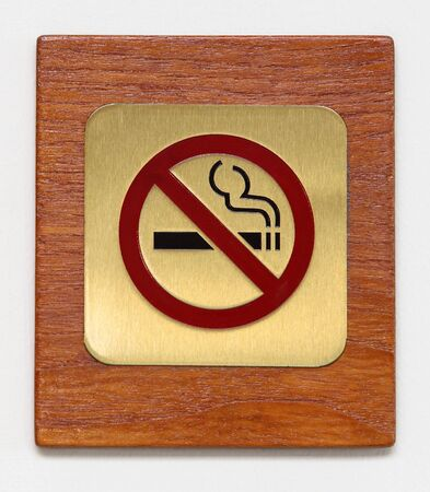 brass no smoking sign on plywood isolated on white photo