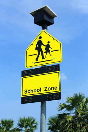 School zone sign, drive slowly and be careful student walking cross the road Stock Photo