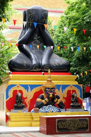 Phra Pidta (closed eyes buddha) and Phra Rahu at Thai temple photo