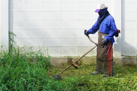 Worker mowing weed near the fence with mowing machine Stock Photo - 16723600