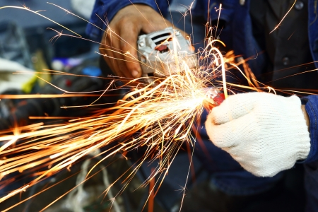 Worker grinding steel pipe with Electric Angle Grinder Stock Photo - 16947097