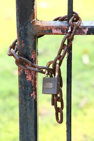 Antique and rusty key and chain on old iron fence photo