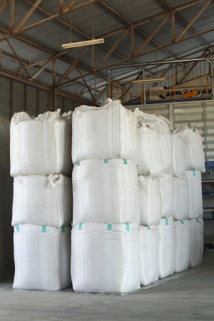 stack of big bag contain rice in warehouse
