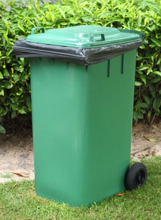 Green bin with black garbage bag  photo