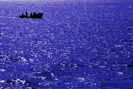 Abstract deep blue sea with Silhouettes boat photo