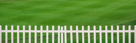 Green lawn and white wood fence photo