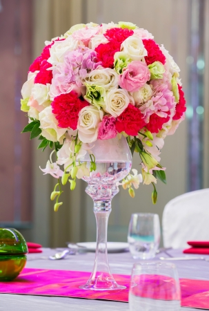 Flower bouquet in glass vase on dining table photo
