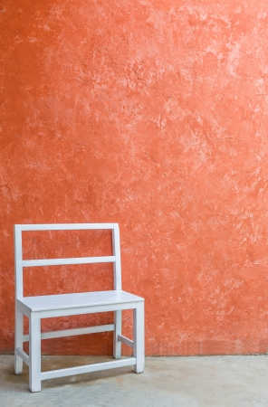 White wood chair and grunge orange color wall photo
