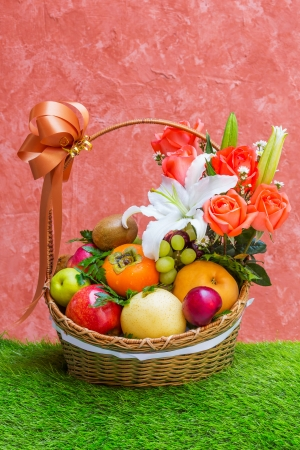 Basket of fruit and flower on green grass and grunge wall photo