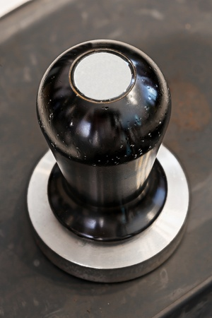 Old and stained stainless steel coffee tamper on rubber sheet photo