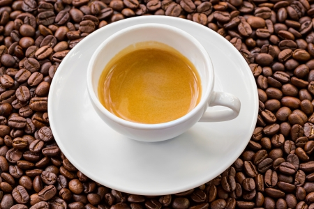 Espresso with golden crema and coffee bean background photo