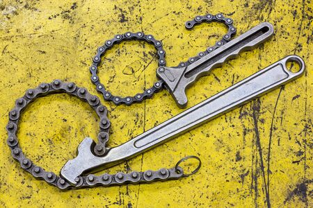 Old and dirty chain wrench on yellow grunge flooe Stock Photo - 17921284