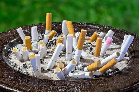 Cigarettes butt in ashtray isolated on green background photo