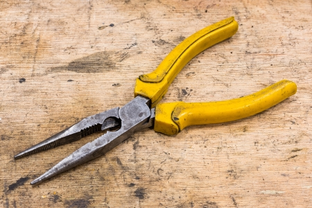 Old and dirty Needle Nose Pliers on grunge wood table Stock Photo - 17921170