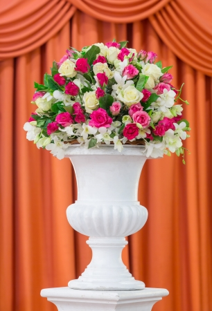 Bouquet of flowers in old fashion vase isolated on red curtain photo
