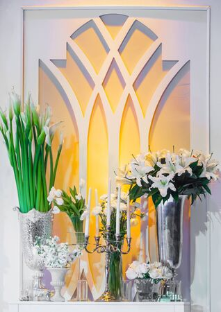 sconce: White flowers such as Calla lily and rose with candles and sconce on white window