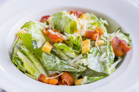 salad dressing: Caesar salad served in white dish Stock Photo