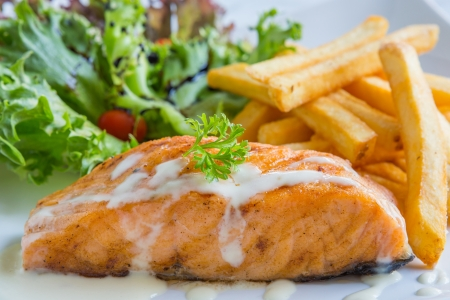Salmon steak served with french fried and lettuce photo