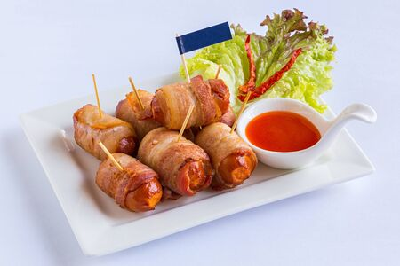 Deep fried sausages rolled in bacon served with lettuce and chili sauce photo