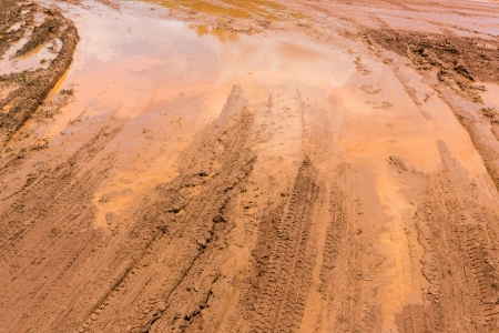 Wheel tracks on red color marshy road after raining Stock Photo - 19223457