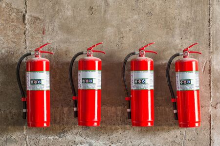 Old fire extinguishers attached on the grunge concrete wall photo