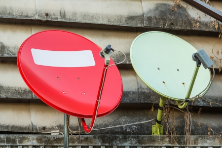 installed: Red and green satellite dishes installed on old building Stock Photo