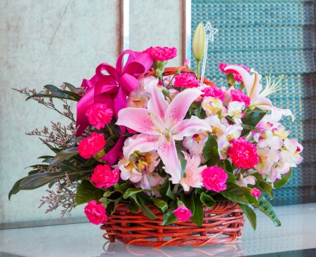 floral arrangement: Bouquet of lily and carnation flower in wicker basket Stock Photo
