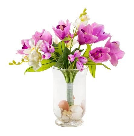 Bouquet of tulip and orchid in glass vase decorated with stone and sea shell isolated on white