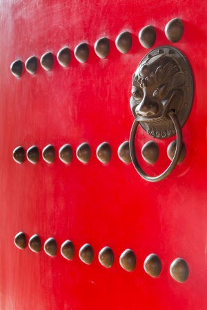 Red color chinese temple door decoration with brass bullet and handle photo