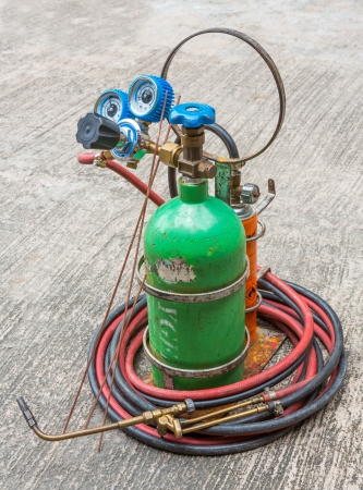 close up small gas welding kit on grunge concrete floor photo