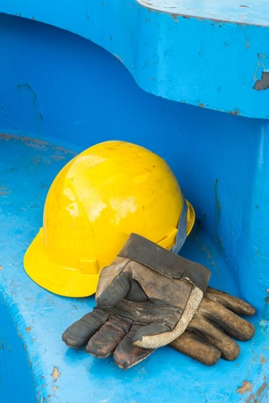 Close up dirty leather gloves and safety helmet using in construction site photo