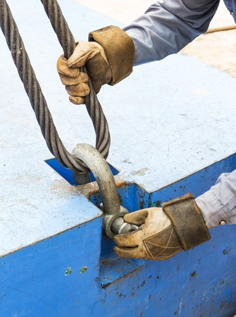 close fitting: Close up worker fitting bolt anchor shackle with wire rope sling on crane counter weight Stock Photo