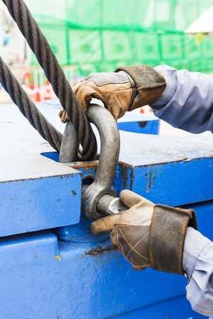 shackle: Close up worker fitting bolt anchor shackle with wire rope sling on crane counter weight Stock Photo