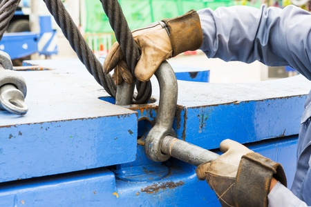 Close up worker fitting bolt anchor shackle with wire rope sling on crane counter weight photo