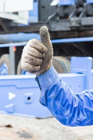 Worker show his thumb in grunge cloth glove for liked sign, mean good or like photo
