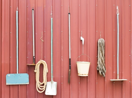 Farm tools hang on red barn wall photo