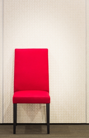 Red elegance chair on carpet floor near metal wall photo