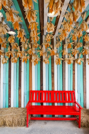 Red color chair in farm near straw bales and dry corn hang from ceiling photo