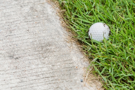 Close up dirty golf ball on grass near the cart path Stock Photo