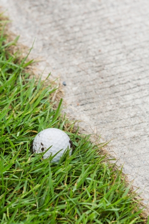 Close up dirty golf ball on grass near the cart path photo
