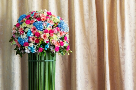 Beautiful flower bouquet and elegant curtain background photo