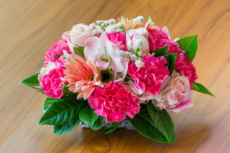 Close up beautiful flower bouquet on wooden table photo