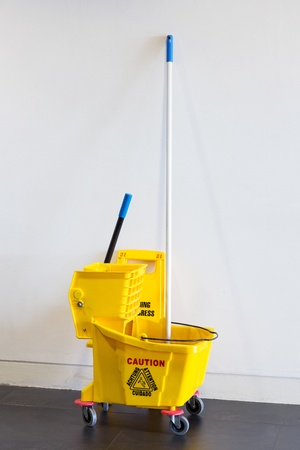 Mop bucket and wringer with caution sign on black floor in office building photo