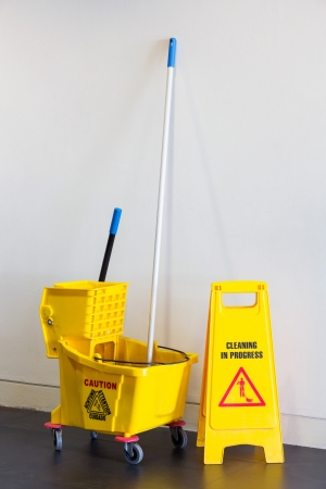 cleaning background: Mop bucket and wringer with caution sign on black floor in office building Stock Photo