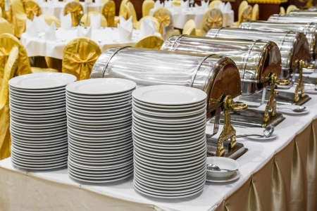 Close up white dishes and warming trays for buffet line photo